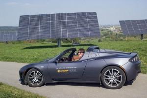 Deger-Ingenieur Simon Hänel im Elektro-Sportwagen seines Chefs – vor Deger-Trakern, die den Strom für das Fahrzeug gewinnen. Bild: Andreas Ellinger